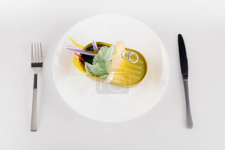 Photo for Top view of tin with plastic rubbish on plate near fork and knife on white, ecology concept - Royalty Free Image