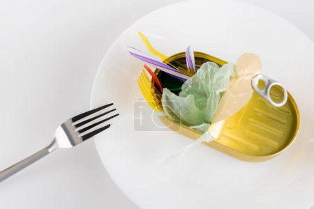 Photo for Tin with polyethylene garbage on plate near fork on white, ecology concept - Royalty Free Image