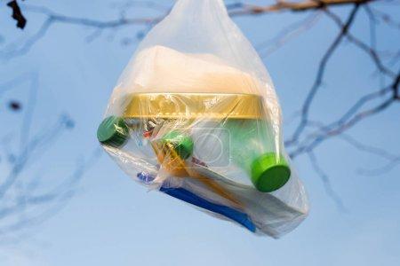 Polyethylen-Beutel mit Dosen und Plastikflaschen vor blauem Himmel, ökologisches Konzept