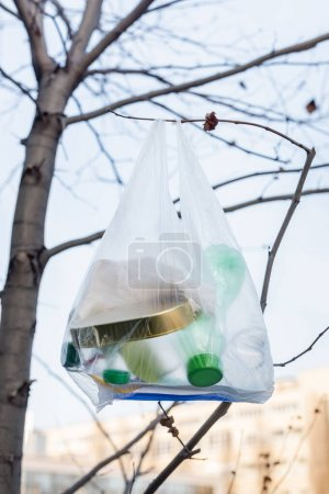 cellophane bag with plastic bottles and tin on tree, ecology concept