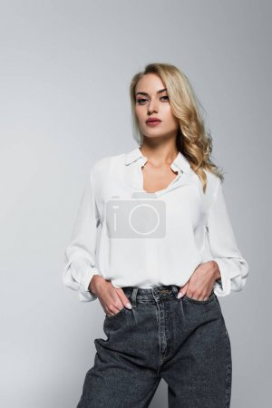 Photo for Young blonde woman in white shirt posing with hands in pockets isolated on grey - Royalty Free Image