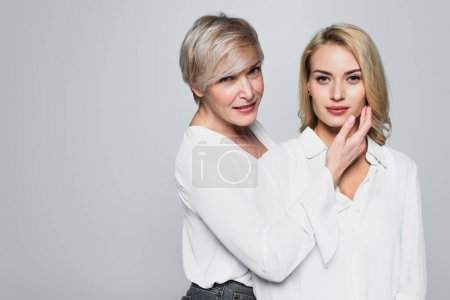 middle aged, stylish woman touching face of young daughter isolated on grey