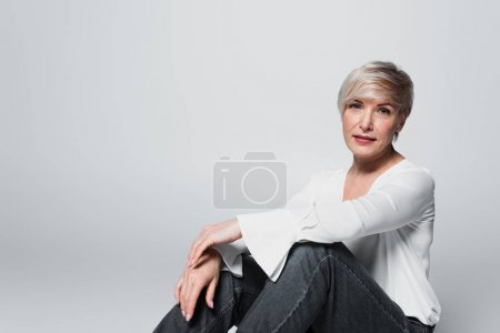 mature woman in white blouse and jeans looking at camera while sitting isolated on grey