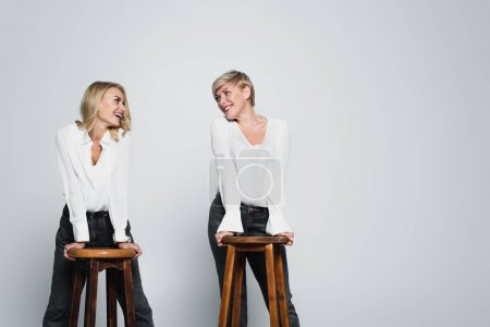 Photo pour Joyful mother and daughter smiling at each other while posing near high chairs on grey - image libre de droit