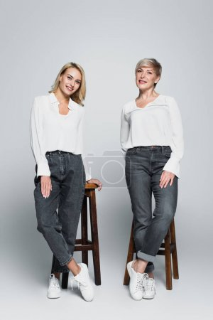 full length view of smiling mother and daughter in trendy clothes posing near high stools on grey