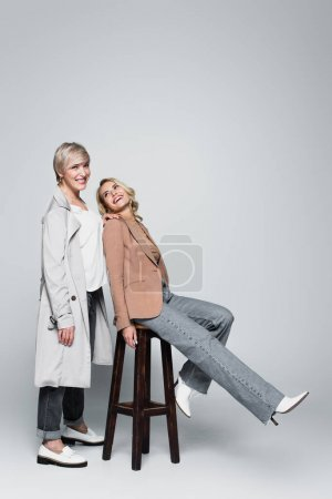 young, cheerful woman sitting on high stool and looking at mother on grey