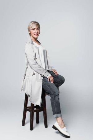 aschblonde Frau im trendigen Herbst-Outfit sitzt auf hohem Hocker auf grau