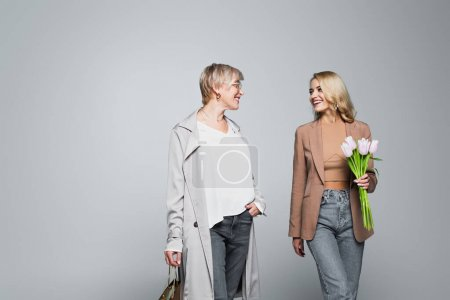 Photo for Happy mother and daughter with shopping bag and tulips looking at each other on grey - Royalty Free Image