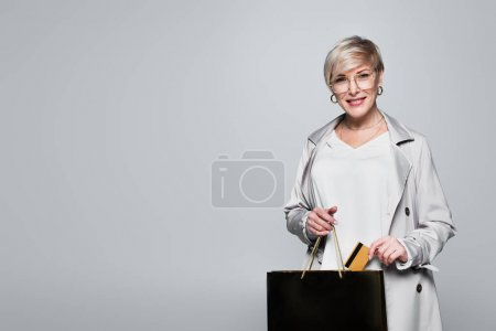 Photo pour Smiling, fashionable woman putting credit card into shopping bag isolated on grey - image libre de droit