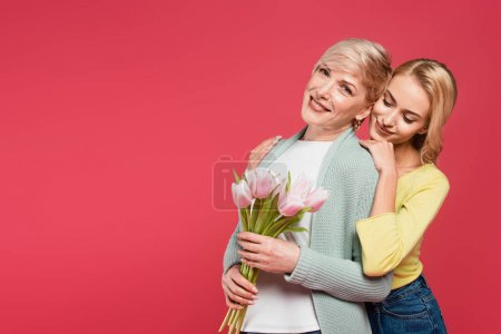 Photo for Happy middle aged woman holding tulips near young, smiling daughter isolated on pink - Royalty Free Image