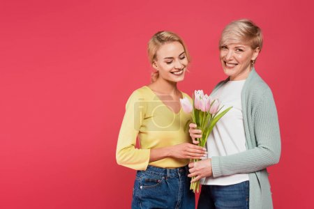 Photo for Cheerful, stylish mother and daughter holding tulips isolated on pink - Royalty Free Image