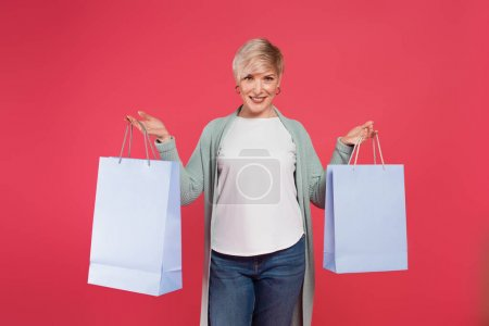 happy, ash-blonde woman holding shopping bags while looking at camera isolated on pink