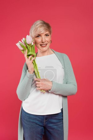 Photo for Stylish, middle aged woman smiling at camera while holding tulips isolated on pink - Royalty Free Image