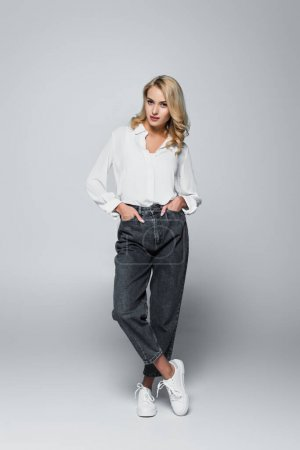 trendy, blonde woman looking at camera while standing with hands in pockets on grey