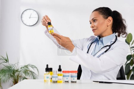 Photo for Brunette african american doctor with stethoscope looking at bottle with cbd lettering - Royalty Free Image