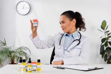 brunette african american doctor with stethoscope looking at bottle with medical cannabis lettering in clinic