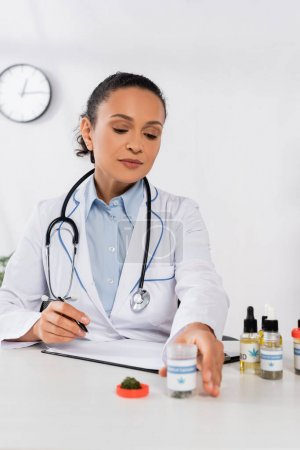 african american doctor with stethoscope reaching bottle with medical cannabis lettering in clinic