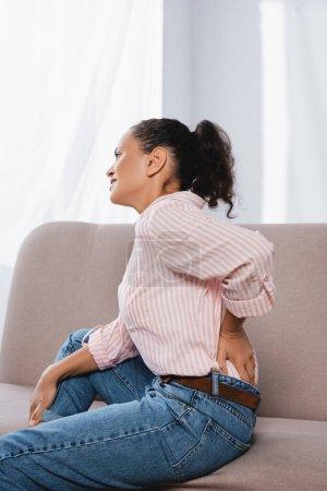 Photo pour Femme afro-américaine souffrant de maux de dos tout en étant assis sur le canapé - image libre de droit