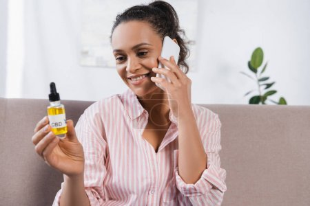 cheerful african american woman holding bottle with cbd and talking on smartphone