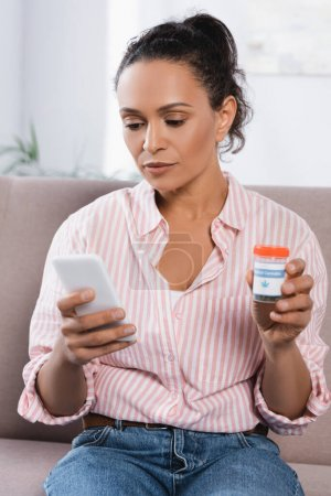 Photo for African american woman holding bottle with medical cannabis and looking at smartphone in living room - Royalty Free Image