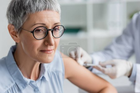 Photo for Mature woman sitting near doctor during vaccination on blurred background - Royalty Free Image