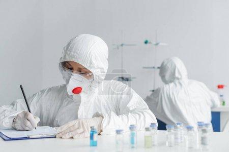 Photo pour Scientifique en uniforme de protection écrit sur presse-papiers près des vaccins et collègue sur fond flou - image libre de droit