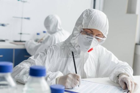 Photo for Scientist writing on clipboard near colleague on blurred background in laboratory - Royalty Free Image