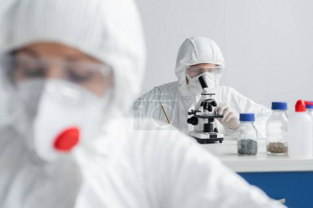 Scientist using microscope while working near colleague on blurred foreground