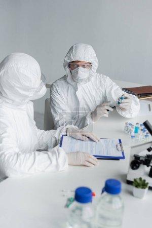 Photo pour Scientifiques travaillant avec des vaccins et des presse-papiers près du microscope au premier plan flou - image libre de droit