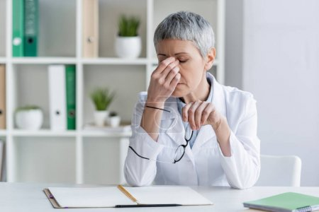 Exhausted doctor holding eyeglasses near working table