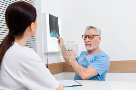 middle aged traumatologist showing x-ray to brunette woman on blurred foreground