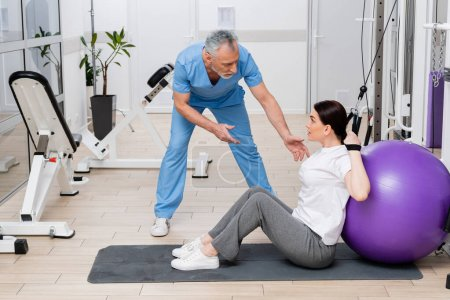middle aged rehabilitologist talking to woman sitting on fitness man in hospital gym