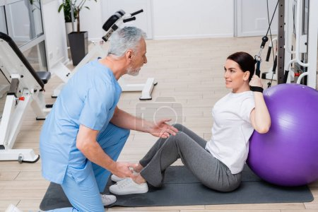 mature trainer instructing woman sitting near fitness ball in rehabilitation center