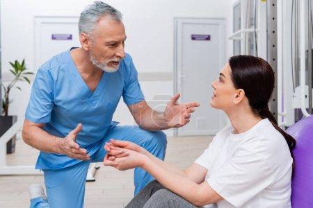 Reife Trainerin gestikuliert im Gespräch mit Frau in Reha-Zentrum