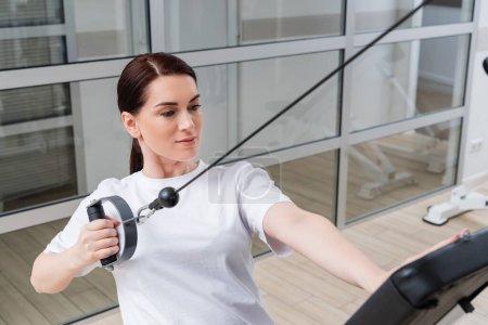 Brünette Frau im weißen T-Shirt trainiert in Reha-Zentrum