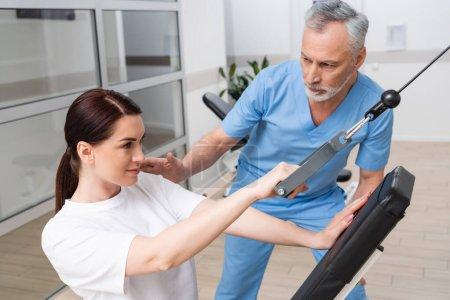 mature rehabilitologist assisting woman training in rehabilitation center