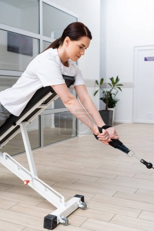 woman training on pull cable exercising machine during rehabilitation