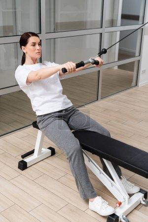 Photo pour Femme concentrée en vêtements de sport travaillant sur la machine d'exercice de corde de traction - image libre de droit
