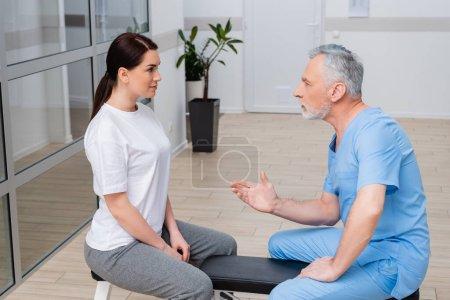 Photo pour Mature réhabilitologue parler à jolie femme tout en étant assis sur le banc d'exercice - image libre de droit
