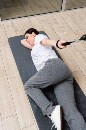 Photo pour Vue grand angle de la femme s'entraînant sur la machine d'exercice de corde de traction tout en étant couché sur le tapis de fitness - image libre de droit