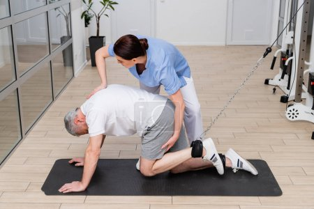 rehabilitologist assisting mature man working out on fitness mat