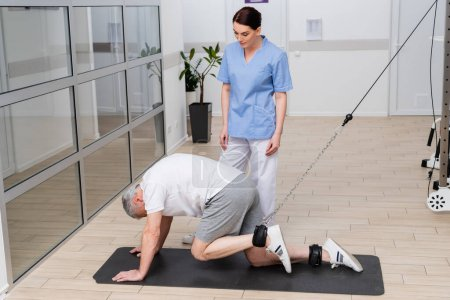 brunette physical instructor assisting mature man working out in rehabilitation center