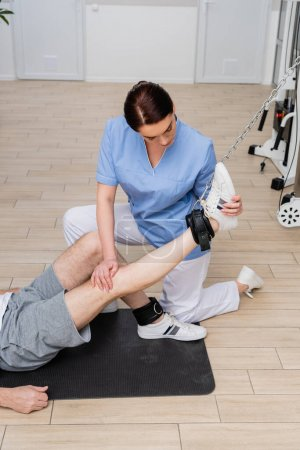 physiotherapist stretching leg of man training in rehabilitation center