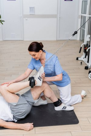 brunette rehabilitologist assisting man working out on fitness mat