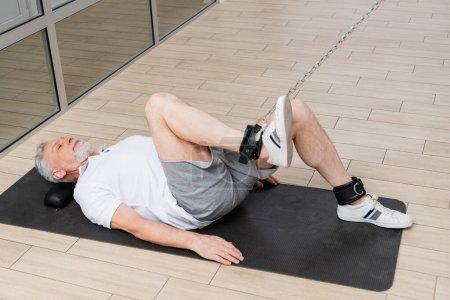 Photo pour Mature homme couché sur tapis de remise en forme tout en travaillant jambe sur la corde de traction machine d'exercice - image libre de droit