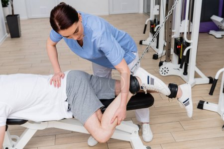 brunette physiotherapist stretching leg of man training in rehabilitation center