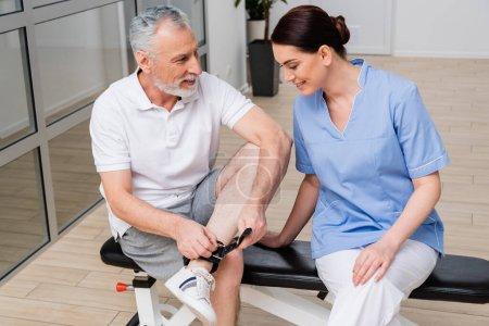 Photo pour Homme souriant détacher ceinture en cuir sur la jambe tout en parlant à brunette réhabilitologue - image libre de droit