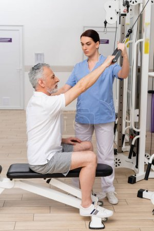 brunette rehabilitologist assisting mature man training on pull cable exercising machine