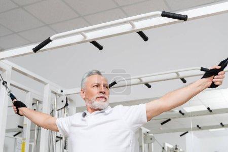 Photo pour Mature homme formation sur corde de traction machine d'exercice dans le centre de réadaptation - image libre de droit