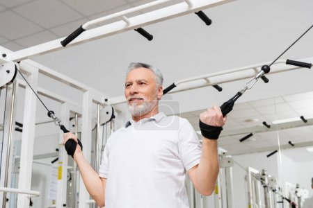 smiling man working out in hospital gym during physical rehabilitation